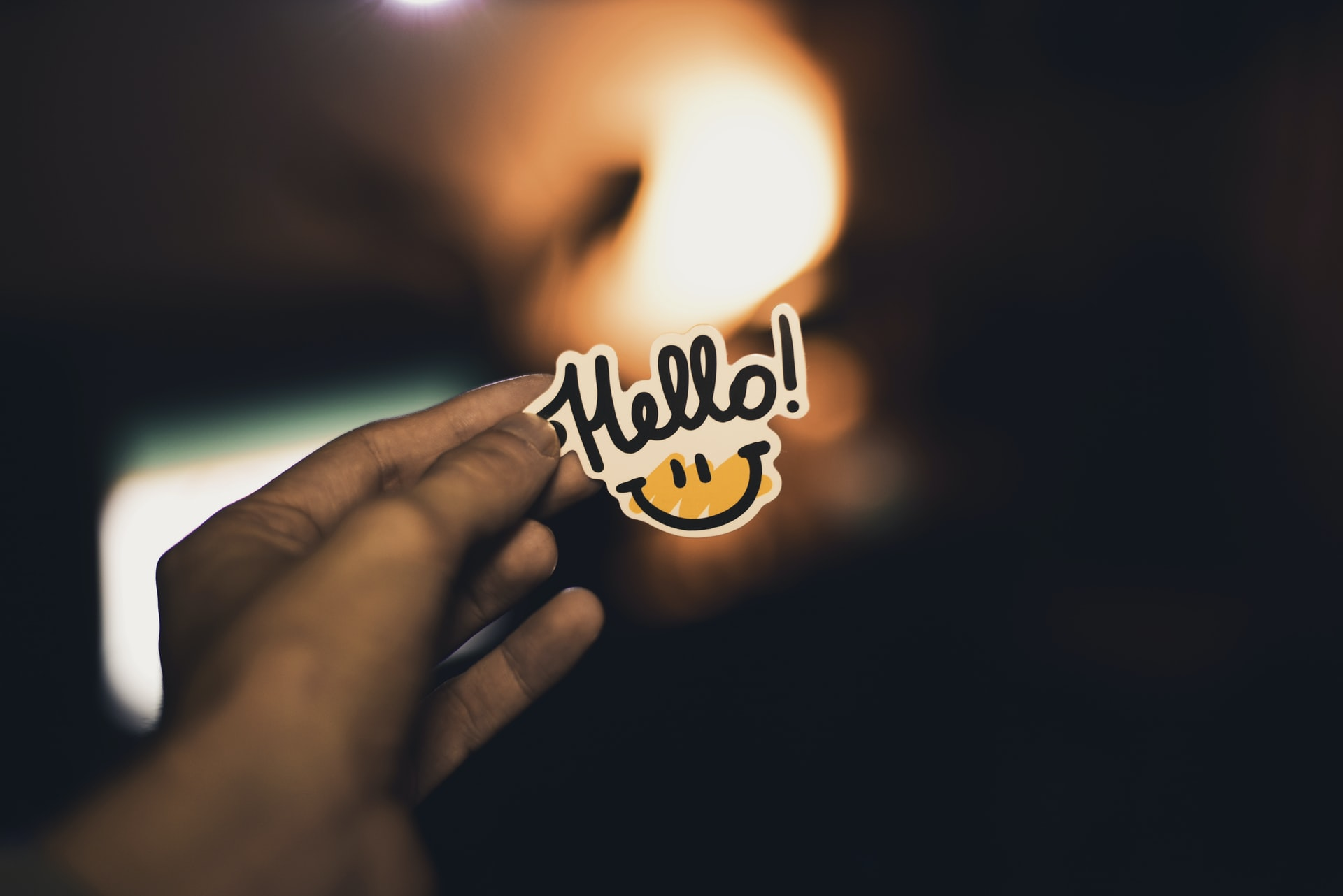 "A person holding a ""hello"" sticker."