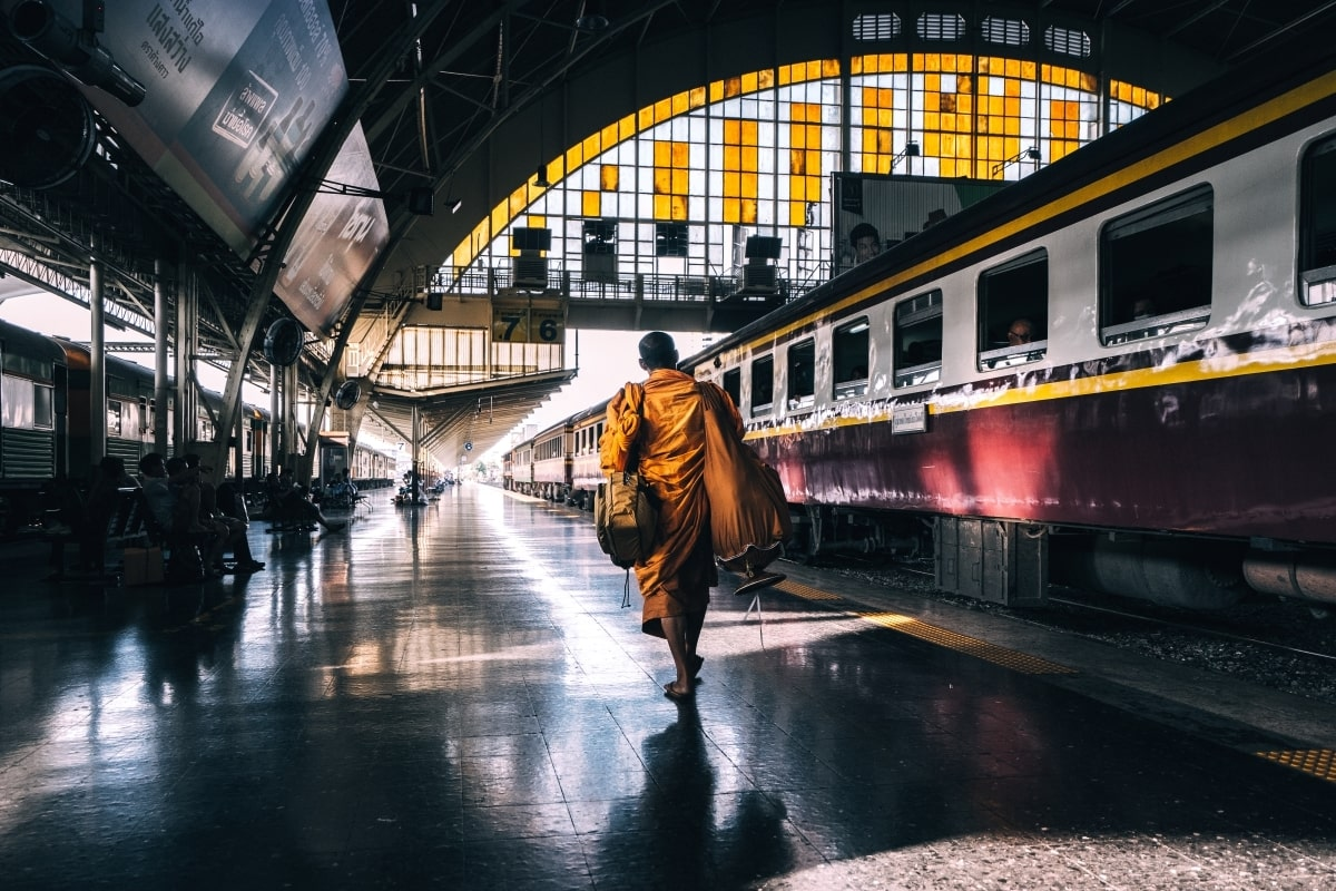 """""""a monk in yellow robe walks through Bangkok's old train station to board his train"""""""
