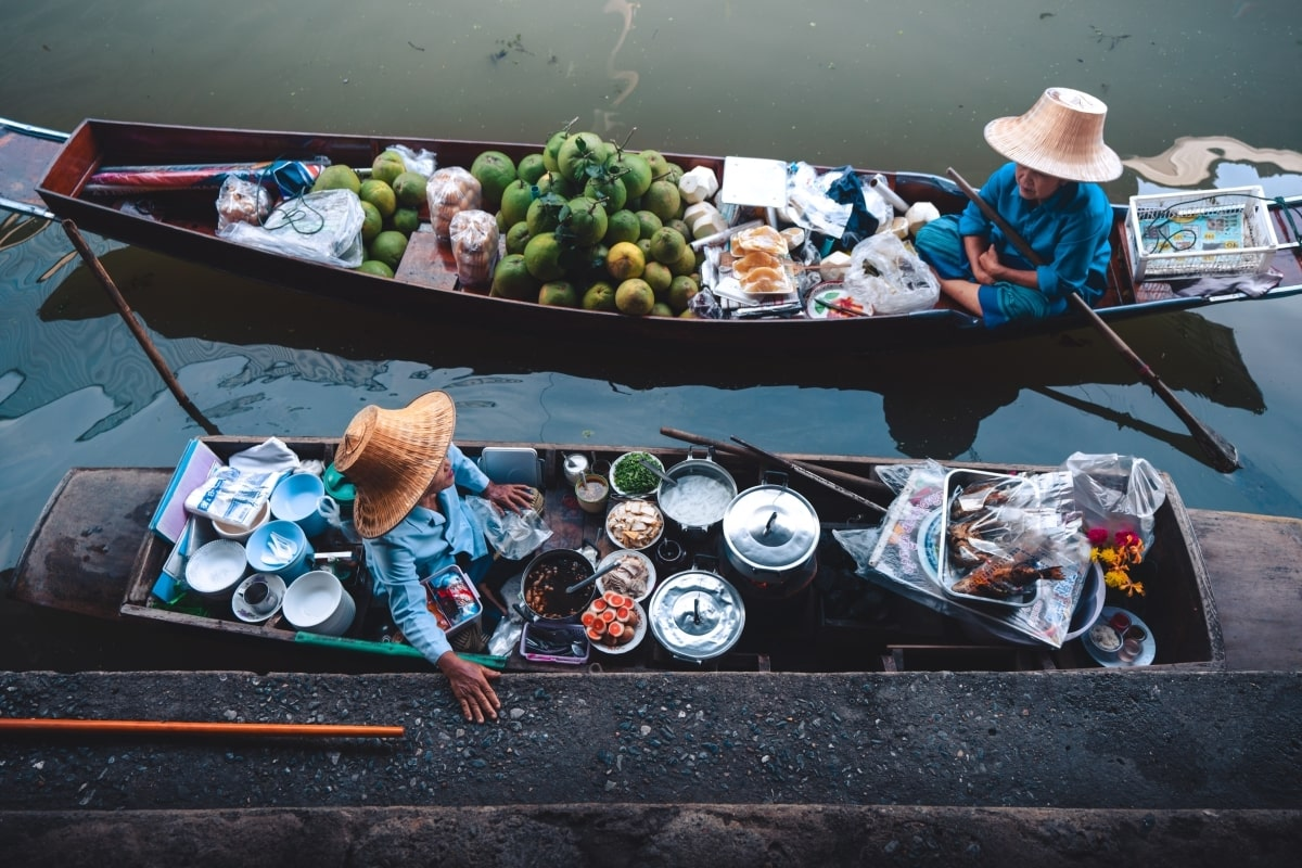 """""""Female traders in boats laden with local food and fruits at the floating market of Thailand"""""""